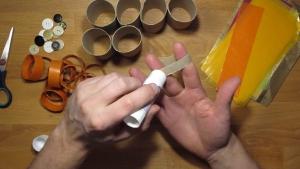 smeer de kokertjes wc-papier-rolletjes in door twee vingers door het kokertje te steken.