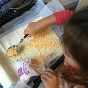 kies een lekkere kaassoort uit en laat je kind deze over het bladerdeeg strooien