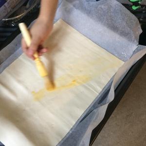 Laat je kind het bladerdeeg uitrollen op een bakpapier en insmeren met eigeel